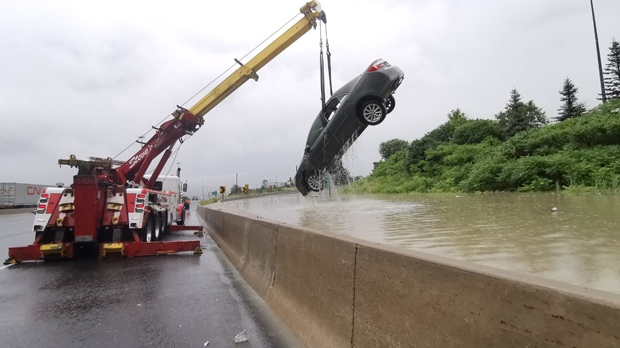 A heavy lift truck raises a Toyota sedan out of a flooded off ramp at Highway 401 and Islington Ave. on July 17, 2019. (Sonny Subra)