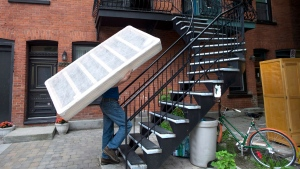 """A man carries a boxspring up a set of stairs on what has become known as """"Moving Day,"""" in Montreal, on July 1, 2013. A new analysis of the country's rental market suggests that a minimum-wage worker can't afford the rent in all but a few neighbourhoods nationwide, and raises questions about a promised federal rent supplement. THE CANADIAN PRESS/Graham Hughes"""