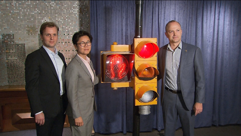 Councillors Joe Cressy (left), Kristyn Wong-Tam (middle) and Mike Layton pose next to a traffic light following a news conference at city hall on Thursday.