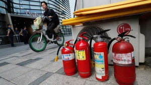 Fire extinguishers are placed near a building where the Japanese embassy is located in Seoul, South Korea, Friday, July 19, 2019. South Korean police say a man has set himself on fire in front of the Japanese Embassy in Seoul amid rising trade disputes between Seoul and Tokyo. (AP Photo/Ahn Young-joon)
