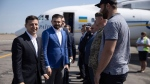 Ukrainian President Volodymyr Zelenskiy, left, smiles as he speaks to local officials upon his arrival to the Zaporizhye region, Ukraine, Thursday, July 18, 2019. Zelenskiy's party is showing the most support in opinion polls ahead of Sunday's snap parliamentary elections, but obtaining a solid majority in the Verkhovna Rada is far from certain. (Ukrainian Presidential Press Office via AP)