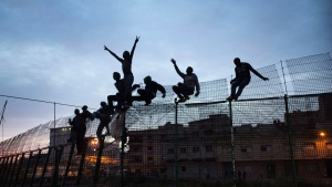 In this Friday, March 28, 2014, file photo, Sub-Saharan migrants climb over a metallic fence that divides Morocco and the Spanish enclave of Melilla. Since the early 1990s, Spain has built six-meter (20-foot) layered border fences around its two North African enclaves, Ceuta and Melilla, to help dissuade migrants, now mostly from sub-Saharan countries, from entering the cities from Morocco in the hope of reaching a better a life in Europe. (AP Photo/Santi Palacios, File)