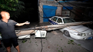 A resident points to a car smashed by a fallen electricity pole in the aftermath of a blast at a nearby gas plant in Yima city central China's Henan province during the early hours of Saturday, July 20, 2019. The Friday evening explosion shattered windows 3 kilometers (1.9 miles) away, and knocked off doors inside buildings, killing some and injuring others. (Chinatopix via AP)