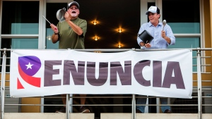 Demonstrators bang on pots, from the balcony of their apartment as they protest against governor Ricardo Rossello, in San Juan, Puerto Rico, Friday, July 19, 2019. Protesters are demanding Rossello step down for his involvement in a private chat in which he used profanities to describe an ex-New York City councilwoman and a federal control board overseeing the island's finance. (AP Photo/Dennis M. Rivera Pichardoi)