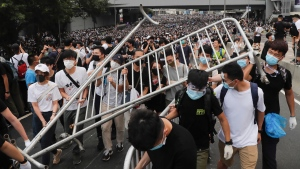 In this Wednesday, June 12, 2019, file photo, protesters carry barricades as they march toward the Legislative Council in Hong Kong. Hundreds of protesters surrounded government headquarters in Hong Kong on Wednesday as the administration prepared to open debate on a highly controversial extradition law that would allow accused people to be sent to China for trial. (AP Photo/Kin Cheung, File)