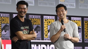 "Destin Daniel Cretton, left, and Simu Liu speaks during the ""Shang-Chi and The Legend of the Ten Rings"" portion of the Marvel Studios panel on day three of Comic-Con International on Saturday, July 20, 2019, in San Diego. (Photo by Chris Pizzello/Invision/AP)"