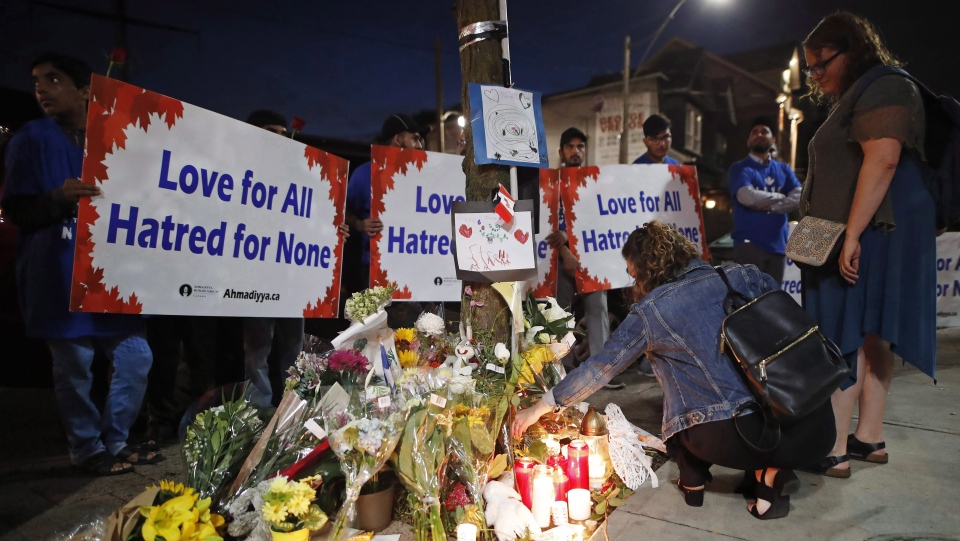 People place flowers and candles at a makeshift memorial remembering the victims of a shooting on Sunday evening on Danforth, Ave. in Toronto on Monday, July 23, 2018. THE CANADIAN PRESS/Mark Blinch