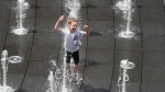 Charles Mitchell runs through a fountain to cool off outside of Wrigley Field before a baseball game between the Chicago Cubs and the San Diego Padres, Friday, July,19, 2019, in Chicago. (AP Photo/David Banks)