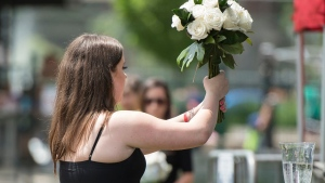 Quinn Fallon carries a bouquet of flowers to the stage, to honour her late sister Reese Fallon, during the one year commemoration of the Danforth shooting at Withrow Park in Toronto on Sunday, July 21, 2019. THE CANADIAN PRESS/ Tijana Martin