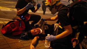 Medical workers help a protester in pain from tear gas fired by policemen on a street in Hong Kong, Sunday, July 21, 2019.  (AP Photo/Bobby Yip)