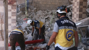 This photo provided by the Syrian Civil Defense White Helmets, which has been authenticated based on its contents and other AP reporting, shows Syrian White Helmet civil defense workers search for victims from under the rubble of a destroyed building that hit by Syrian government and Russian airstrikes, in the northern town of Maaret al-Numan, in Idlib province, Syria, Monday, July 22, 2019.  (Syrian Civil Defense White Helmets via AP)