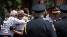 Claudine Debeaumont, the mother of Reese Fallon, who was killed during the Danforth shooting one year ago, receives a hug during commemoration of the Danforth shooting at Withrow Park in Toronto on Sunday, July 21, 2019. THE CANADIAN PRESS/ Tijana Martin