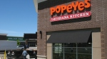 A worker carries garbage to a bin as construction takes place on Popeyes Louisiana Kitchen restaurant in Bowmanville, Ont. on Saturday June 3, 2017. Restaurant Brands International Inc. says it has an agreement to develop and open more than 1,500 Popeyes restaurants in China over the next 10 years.THE CANAIDAN PRESS/Doug Ives
