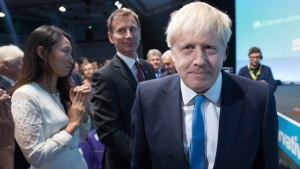 Boris Johnson walks to the stage, as rival Jeremy Hunt looks on after the announcement of the result in the ballot for the new Conservative party leader, in London, Tuesday, July 23, 2019.  (Stefan Rousseau/Pool photo via AP)