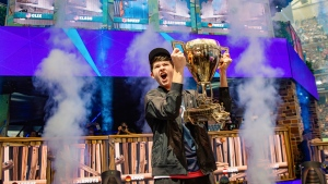 "In this Sunday, July 28, 2019 photo, Kyle Giersdorf celebrates as he holds up the trophy after winning the Fortnite World Cup solo finals in New York. Giersdorf, of Pottsgrove, Pa. who goes by the name ""Bugha"" when competing, racked up the most points and won $3 million as the first Fortnite World Cup solo champion. (Epic Games via AP)"