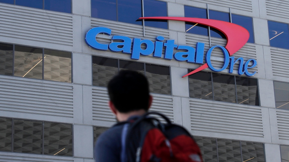 In this July 16, 2019, photo, a man walks across the street from a Capital One location in San Francisco. Federal prosecutors say a woman charged in a massive data breach at Capital One may have hacked more than 30 other organizations. (AP Photo/Jeff Chiu)