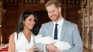 In this Wednesday May 8, 2019 file photo, Britain's Prince Harry and Meghan, Duchess of Sussex, during a photocall with their newborn son, in St George's Hall at Windsor Castle, England. Prince Harry says he and wife Meghan will have no more than two children because of concerns for the environment. Harry interviewed primatologist Jane Goodall for Vogue magazine, and said becoming a father to baby Archie in May had changed his perspective. (Dominic Lipinski/Pool via AP, file)