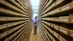 In this May 8, 2008 file picture Gary Mokotoff, a Jewish genealogist from New Jersey, takes a look at name registers at the International Tracing Service (now renamed the Arolsen Archives - International Center on Nazi Persecution) in Bad Arolsen, central Germany. (AP Photo/Michael Probst, file)
