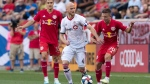 Toronto FC midfielder Michael Bradley, center, fights for the ball against New York Red Bulls midfielder Marc Rzatkowski, right, and Aaron Long, left, during the first half of an MLS soccer match, Saturday, Aug. 3, 2019, in Harrison, N.J. (AP Photo/Mary Altaffer)
