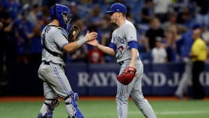 Toronto Blue Jays relief pitcher Ken Giles, right, and catcher Reese McGuire shake hands after closing out the Tampa Bay Rays during a baseball game Wednesday, Aug. 7, 2019, in St. Petersburg, Fla. (AP Photo/Chris O'Meara)
