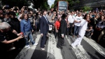 Fans dressed as lookalikes walk across the Abbey Road zebra crossing on the 50th anniversary of British pop musicians The Beatles doing it for their album cover of 'Abbey Road' in St Johns Wood in London, Thursday, Aug. 8, 2019. They aimed to cross 50 years to the minute since the 'Fab Four' were photographed for the album. (AP Photo/Kirsty Wigglesworth)