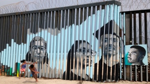 The mural shows faces of people deported from the U.S. with barcodes that activate first-person narratives on visitors' phones. Lizbeth De La Cruz Santana conceived the interactive mural in Tijuana as part of doctoral dissertation at the University of California, Davis. (AP Photo/Elliot Spagat)