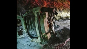 This Aug. 3, 2019 photo from the Hoopa Fire Department shows a Humboldt County Sheriff's Department patrol car after it was struck by a falling bear and then hit an embankment, rolled onto its side and burst into flames, near Hoopa, Calif., in Northern California.  (Rod Mendes/Hoopa Fire Department via AP)