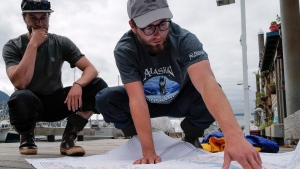 In this Thursday, Aug. 2, 2019 photo, Liam Godfrey-Jolicoeur, left, and Jake Dombek, talk at Harris Harbor in Juneau, Alaska, about their nearly two-month long trip up the Inside Passage by canoe. Both are originally from Vermont used the trip to raise money and bring awareness to environmental causes. (Michael Penn/Juneau Empire via AP)