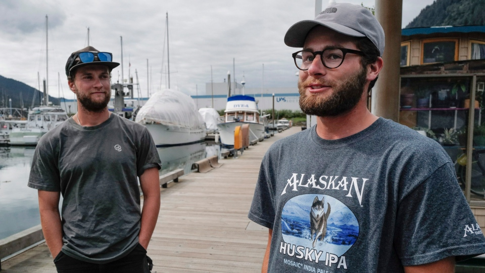 In this Thursday, Aug. 2, 2019 photo Liam Godfrey-Jolicoeur, left, and Jake Dombek, talk at Harris Harbor, in Juneau, Alaska, about their nearly two-month long trip up the Inside Passage by canoe. Both are originally from Vermont used the trip to raise money and bring awareness to environmental causes. (Michael Penn/ Juneau Empire via AP)