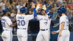 Toronto Blue Jays' Brandon Drury is met by teammates at home plate after hitting a grand slam during fourth inning American League MLB baseball action against the Texas Rangers, in Toronto, Monday, Aug. 12, 2019. THE CANADIAN PRESS/Fred Thornhill