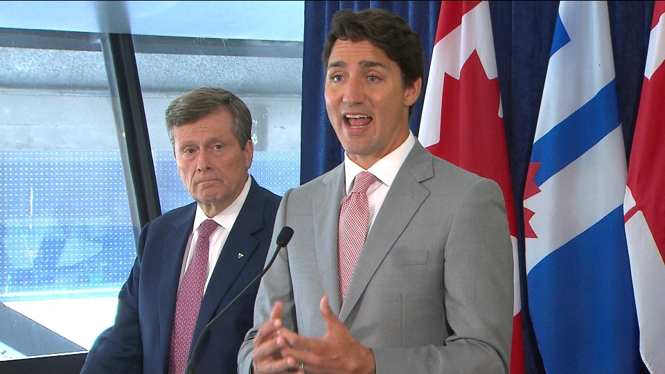 Prime Minister Justin Trudeau speaks with reporters at city hall as Mayor John Tory looks on.