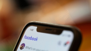 In this Sunday, Aug. 11, 2019, photo an iPhone displays a Facebook page in New Orleans.  Facebook says it paid contractors to transcribe audio clips from users of its Messenger service. (AP Photo/Jenny Kane)