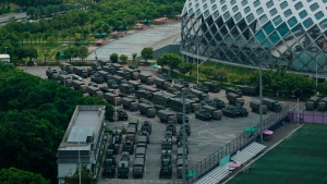 Armored vehicles and troop trucks are parked in a lot by Shenzhen Bay Stadium in Shenzhen, China Friday, Aug. 16, 2019. Armored vehicles belonging to China's paramilitary People's Armed Police were parked in the sports complex across the border in Hong Kong, in what some have interpreted as a threat against pro-democracy protesters. (AP Photo/Dake Kang)