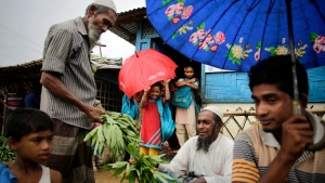 In this Aug. 28, 2018, file photo, Rohingya refugees, in the foreground, sell vegetables as girls take shelter under an umbrella as they leave a makeshift school at Kutupalong refugee camp, where they have been living amid uncertainty over their future after they fled Myanmar to escape violence a year ago, in Bangladesh. Myanmar and Bangladesh are making a second attempt to start repatriating Rohingya Muslims after more than 700,000 of them fled a security crackdown in Myanmar almost two years ago, the U.N. refugee agency said Friday, Aug. 16, 2019. (AP Photo/Altaf Qadri, File)