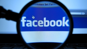 A magnifying glass is posed over a monitor displaying a Facebook page. (AP / Joerg Koch)