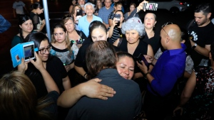 People gather to offer condolences to Antonio Bosco, foreground, husband of Margie Reckard who lost her life during a shooting, Friday, Aug. 16, 2019, in El Paso, Texas. Reckard was killed during the mass shooting on Aug. 3. (AP Photo/Jorge Salgado)