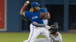 Seattle Mariners' Tim Lopes gets forced out at second base as Toronto Blue Jays' Vladimir Guerrero Jr. turns the double play during first inning American League MLB baseball action in Toronto, Saturday, Aug. 17, 2019. THE CANADIAN PRESS/Fred Thornhill