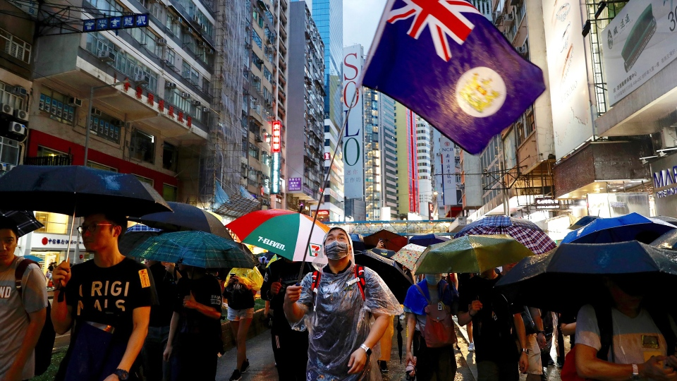 A protester waves a Hong Kong colonial-era flag as others march along a street in Hong Kong, Sunday, Aug. 18, 2019.  (AP Photo/Vincent Yu)