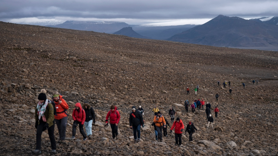 People climb to the top of what once was the Okjokull glacier, in Iceland, Sunday, Aug. 18, 2019. With poetry, moments of silence and political speeches about the urgent need to fight climate change, Icelandic officials, activists and others bade goodbye to the first Icelandic glacier to disappear. (AP Photo/Felipe Dana)