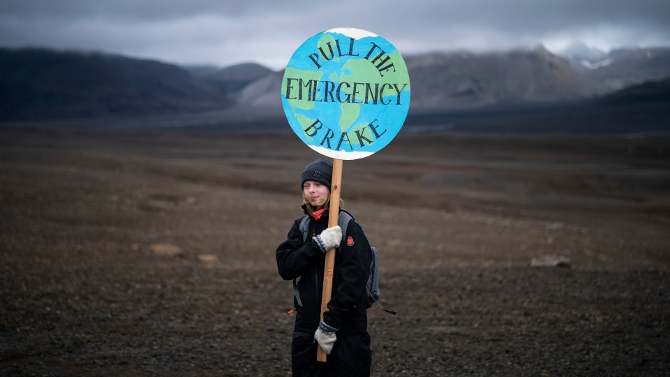 A girl holds a sign that reads 'pull the emergency brake' as she attends a ceremony in the area which once was the Okjokull glacier, in Iceland, Sunday, Aug. 18, 2019. (AP Photo/Felipe Dana)