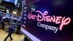 FILE - In this Aug. 8, 2017, file photo, The Walt Disney Co. logo appears on a screen above the floor of the New York Stock Exchange. Disney says its net income fell 39% in the latest quarter. Net income for the fiscal third quarter, which ended June 29, 2019, fell to $1.76 billion, from $2.92 billion last year. (AP Photo/Richard Drew, File)