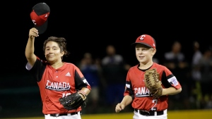 British Columbia's Piero Leon-Carney (10) tips his cap to the crowd as he and Tory Hutchinson run off the field after the final out against Italy in the fourth inning of an elimination baseball game in international pool play baseball game at the Little League World Series tournament in South Williamsport, Pa., Saturday, Aug. 17, 2019. (AP Photo/Tom E. Puskar)