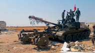 In this Tuesday, Aug. 13, 2019 photo, released by the Syrian official news agency SANA, Syrian army soldiers flash the victory sign as they stand on a tank, in northwestern Syria. Syrian government forces captured five villages in the country's northwest early Wednesday, Aug 14, 2019 inching closer to a major rebel-controlled town that was the scene of a deadly 2017 chemical weapons attack, where thousands of people were fleeing their homes to safer area further north, a war monitor, opposition activists and state media reported. (SANA via AP)