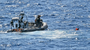 Italian Finance Police rescue a migrant who jumped off the Spanish humanitarian rescue ship Open Arms in a desperate bid to reach the shore of the Sicilian island of Lampedusa, southern Italy, tantalizingly near after 19 days blocked on board in deteriorating conditions by Italy's refusal to open its ports, Monday, Aug. 19, 2019. (AP Photo/Salvatore Allegra)