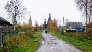 In this photo taken Oct. 7, 2018, a person walks down a street in the village of Nyonoksa, northwestern Russia. The Aug. 8, 2019, explosion of a rocket engine at the Russian navy's testing range just outside Nyonoksa led to a brief spike in radiation levels and raised new questions about prospective Russian weapons. (AP Photo/Sergei Yakovlev)