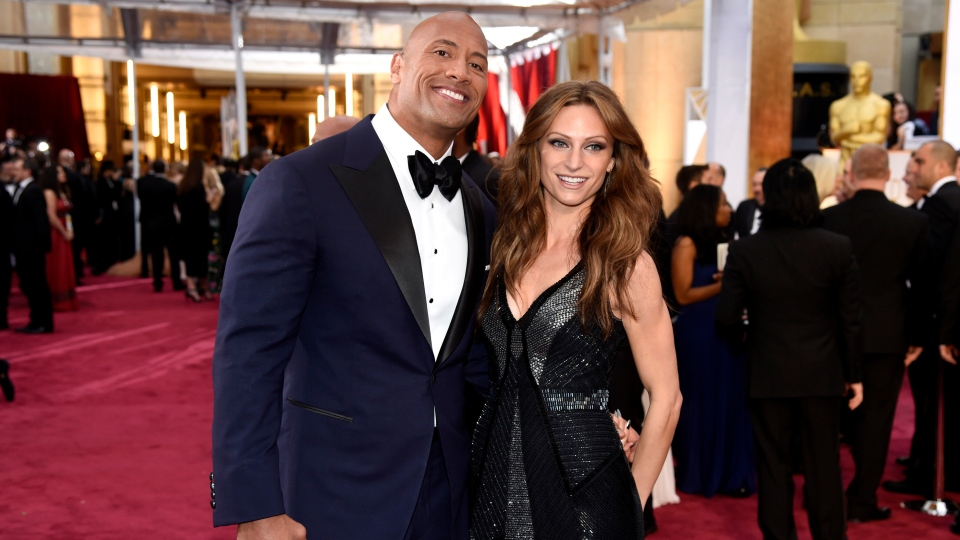 In this Feb. 22, 2015, file photo Dwayne Johnson, left, and Lauren Hashian arrive at the Oscars at the Dolby Theatre in Los Angeles. Johnson announced his wedding to Hashian on Instagram. A photo of the couple was posted on the social media site, showing them both wearing white. The post also said the date of their apparent nuptials, on Sunday, Aug. 18, 2019, in his native Hawaii. (Photo by Chris Pizzello/Invision/AP, File)