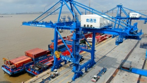 "In this July 18, 2019, file photo, shipping containers are loaded onto a cargo ship at a port in Nantong in eastern China's Jiangsu province. Beijing appealed to Washington on Wednesday, Aug. 21, to ""meet China halfway"" and end a tariff war after President Donald Trump said Americans might need to endure economic pain to achieve longer-term benefits. (Chinatopix via AP)"