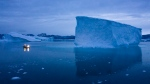 In this Aug. 15, 2019, photo, a boat navigates at night next to icebergs in eastern Greenland.  (AP Photo/Felipe Dana)