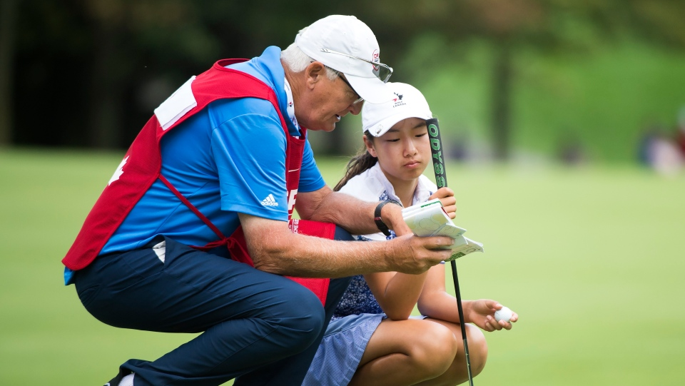 Twelve year-old Canadian Michelle Liu, right, talks with her caddie on the 16th green during first round of the CP Women's Open in Aurora, Ont., on Thursday, Aug. 22, 2019. THE CANADIAN PRESS/Nathan Denette