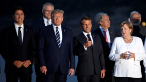 Canadian Prime Minister Justin Trudeau, left, President Donald Trump, French President Emmanuel Macron and German Chancellor Angela Merkel pose during the G7 family photo Sunday, Aug. 25, 2019 in Biarritz. (Christian Hartmann, Pool via AP)